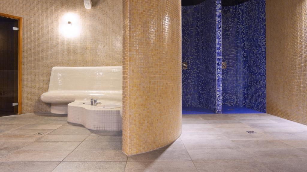 obiekt spa sauna z prysznicami i ławą z misami do moczenia stóp
