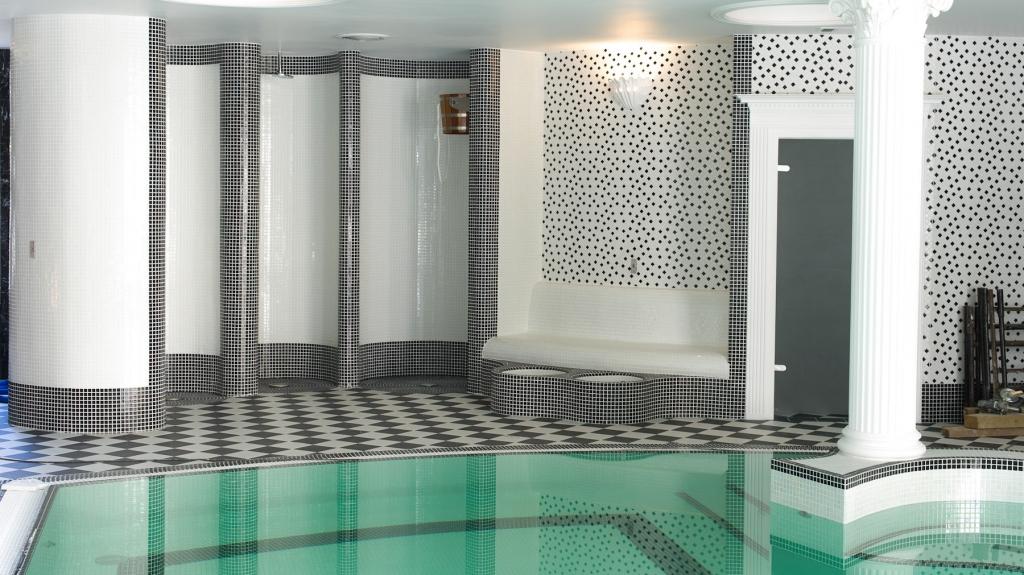 wnętrze basenu hotelowego połączone z prysznicami i i strefą spa
