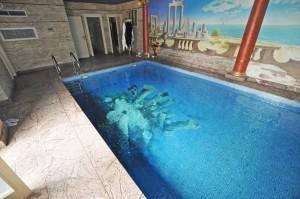 basen prywatny z motywem greckim na dnie i ścianach basenu