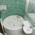 nowoczesny projekt łazienki z wanną z hydromasażem i zieloną mozaiką na ścianie
