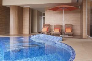 strefa plaży basenu w hotelu drewniane leżaki parasol sauna fińska